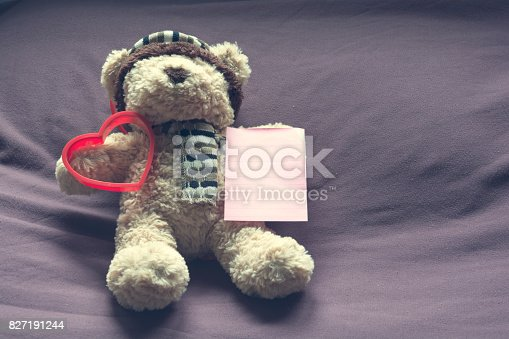 1061427386 istock photo Teddy bear with red heart shape and empty note paper on bed. Valentine concept. 827191244