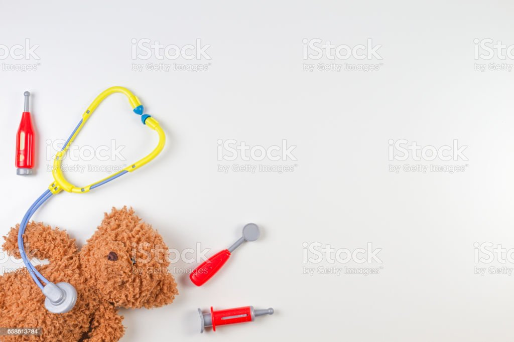 Teddy bear with toy stethoscope and toy medicine tools on a white background. Top view stock photo