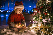 High angle view of girl in red clothes playing by the Christmas tree and waiting for midnight surprise.