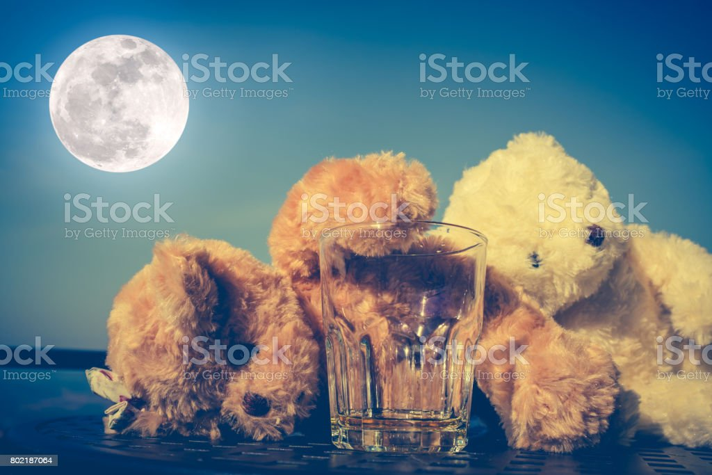 Teddy bears couple very drunk alcoholic with empty glass. stock photo