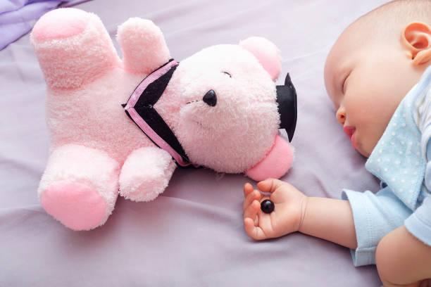 teddy bär auge wurde abgelöst von kleinkind und 10 monate alten baby hand zu schlafen, vorsicht bei erstickungsgefahr für kinder-konzept - nähpuppen stock-fotos und bilder