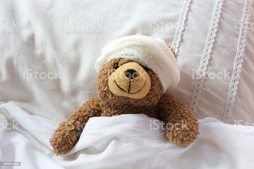 Teddy in bear bed with bandage on head - foto de stock