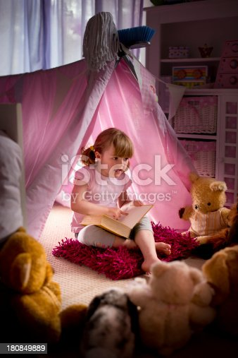 little girl reads a story to all her teddies.