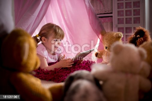 little girl reads a story to all her teddies from a digital tablet.**main teddy in focus is non branded pre-1970**