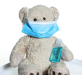Cute teddy bear with his PPE. Surgical face mask and hand sanitiser gel to protect against Coronavirus covid-19 pandemic.