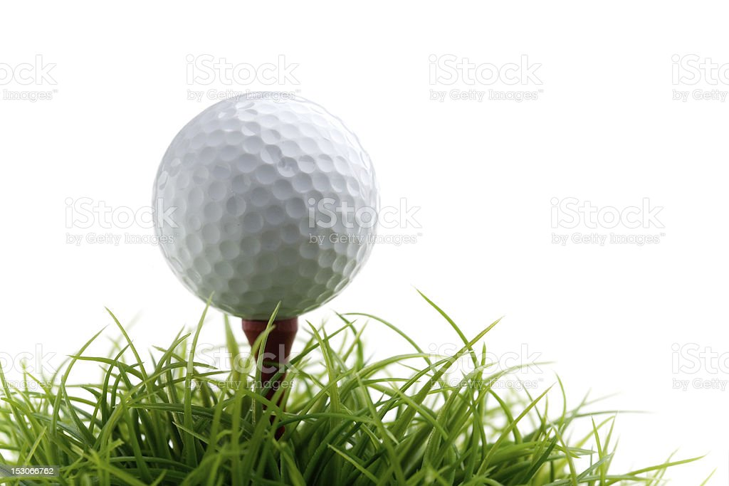 A teed up golf ball on a small patch of green grass stock photo