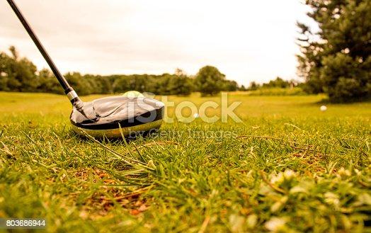 A golf club, driver, gets ready to hit a golf ball down the fairway.