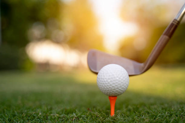 Teeing off with golf club and golf ball stock photo