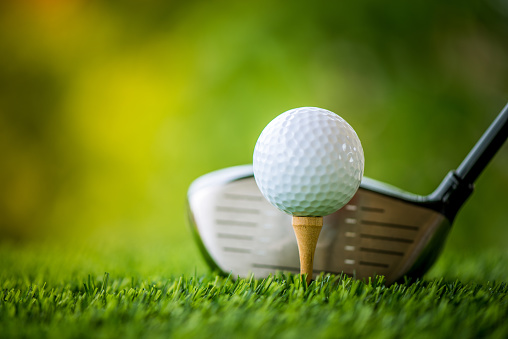 teeing off with golf club and golf ball