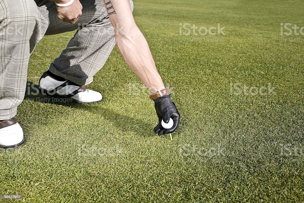 teeing up a golf ball