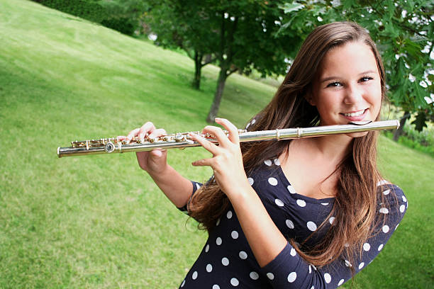 teen Age Girl Playing Traversal Flute Outdoors, Countryside Serene place stock photo