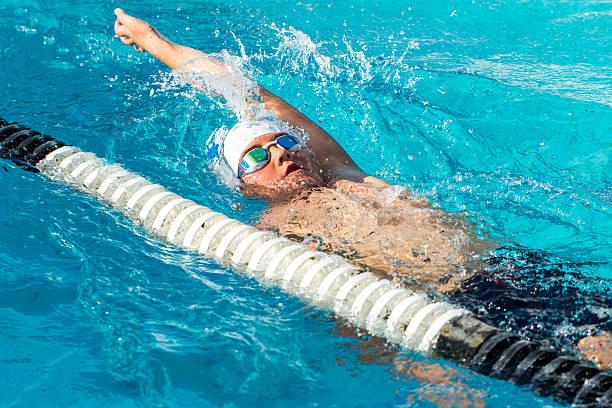 Teen backstroke swimmer in action. stock photo