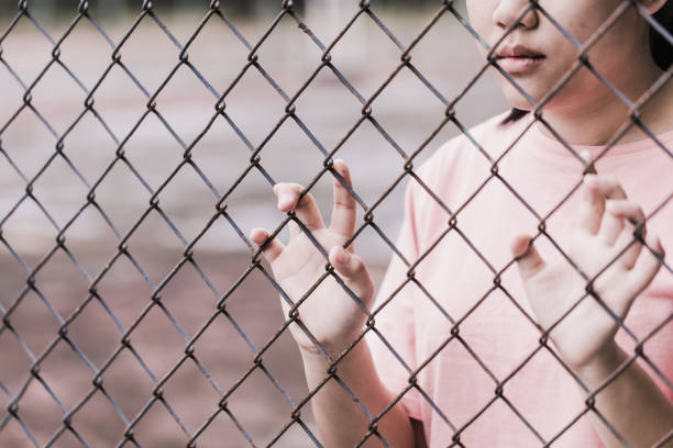 teen behind the cage or woman jailed, unhappy girl hand sad hopeless at fence prison in jail, no free and freedom struggle teen concept. teen behind the cage or woman jailed, unhappy girl hand sad hopeless at fence prison in jail, no free and freedom struggle teen concept. ensnare stock pictures, royalty-free photos & images