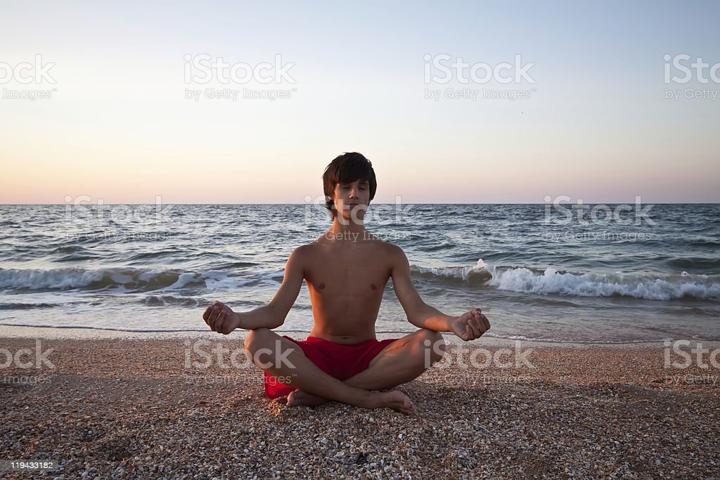 Teen boy at the beach meditating on sunset royalty-free stock photo