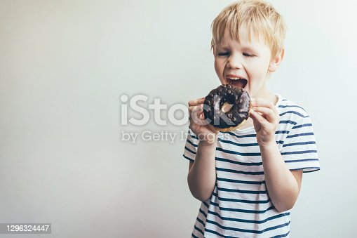 Teen boy bites a chocolate donut. Funny portrait of a child.
