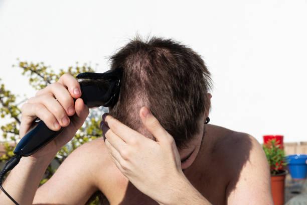 teen boy cutting his hair with a hair clipper - covid hair imagens e fotografias de stock
