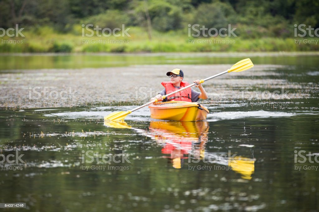 Teen Boy In Kayak A 13 year old boy wnjoying a summer day in a kayak. Active Lifestyle Stock Photo