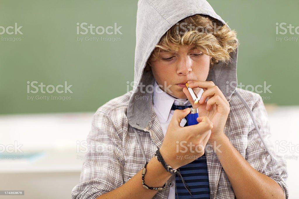 teen boy lighting cigarette stock photo