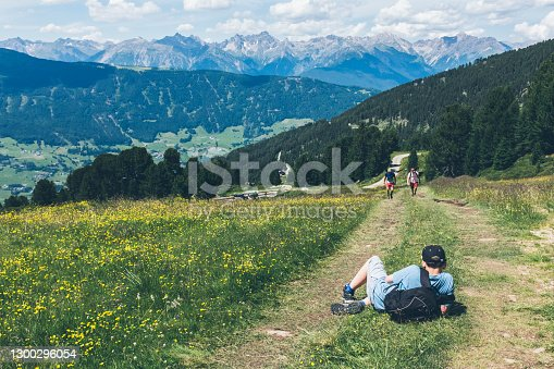 istock Teen boy lying on the dirt road on the slope of the mountains in the green meadow waiting for this father and brother to catch up - they are walking up the mountain with amazing panorama in distance. 1300296054