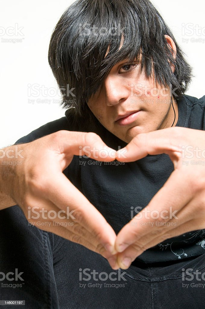 Teen boy making heart shape with hands stock photo