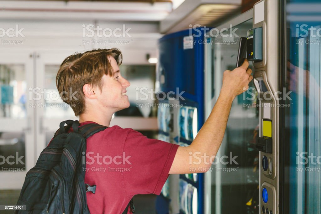 Teen boy paying with mobile phone at vending machine stock photo