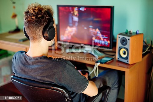 Teen Boy Playing Games on Computer wearing Headphones
