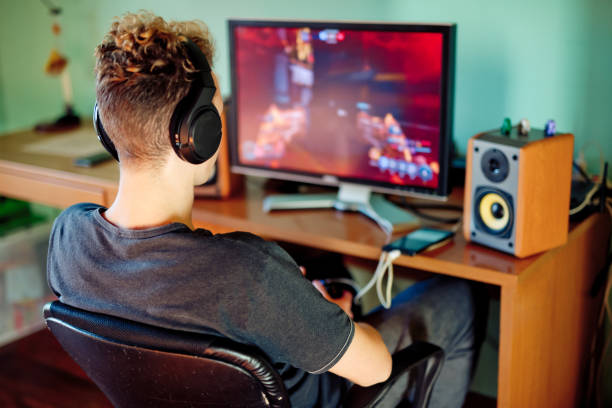 十代少年ヘッドフォンを身に着けているコンピューター上のゲームをプレイ - ゲーム ヘッドフォン ストックフォトと画像
