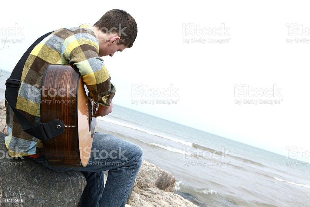 Teen Boy Playing Guitar at Beach royalty-free stock photo