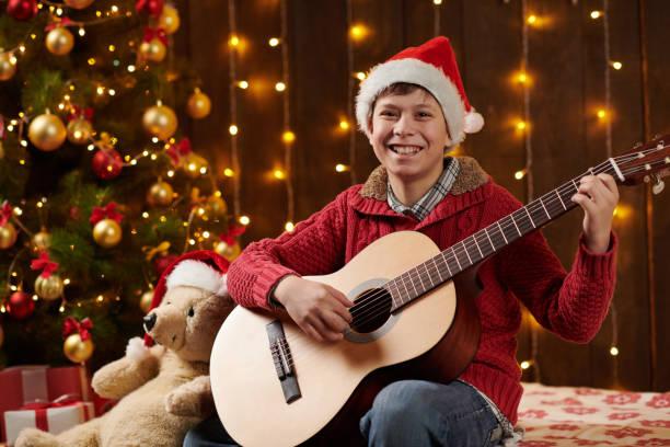 Adolescente niño tocando la guitarra, sentado interior cerca decorado árbol de Navidad con luces, vestido como Santa ayudante - Feliz Navidad y Felices Fiestas! - foto de stock