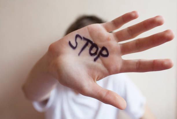 """adolescente niño se protege con la mano en la palma de su inscripción """"parada"""" - human trafficking fotografías e imágenes de stock"""