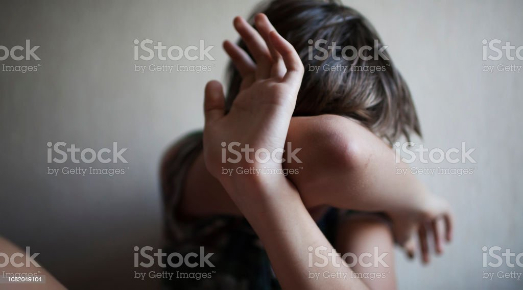 Teen boy protects himself with his hands from violence Teen boy protects himself with his hands from violence isolated Adult Stock Photo