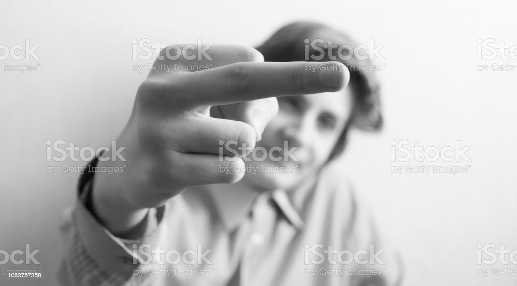 Teen boy shows middle finger gesture isolated