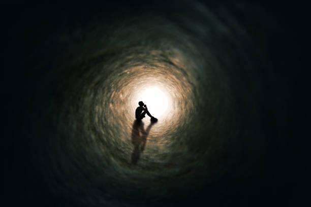 Teen Boy Silhouette Far Away Praying in Tunnel stock photo