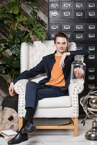 Teen boy sitting in armchair with science attributes as naturalist discoverer