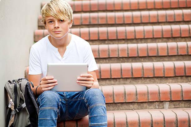 teen boy sitzt auf treppen und mit tablet-computer - liebeskind umhängetasche stock-fotos und bilder