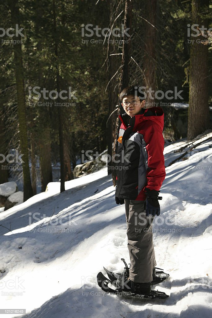 Teen Boy Snowshoeing in Winter stock photo