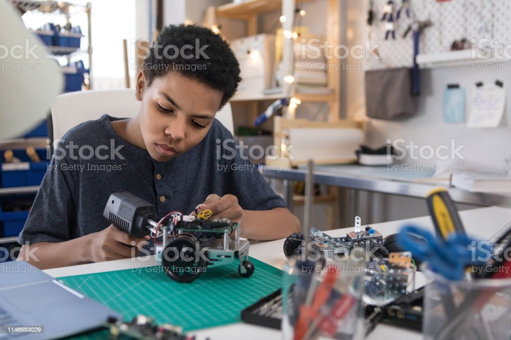 Teen boy solders wires to build robot A serious teen boy uses a soldering gun to connect wires as he builds a robot at home. Adolescence Stock Photo