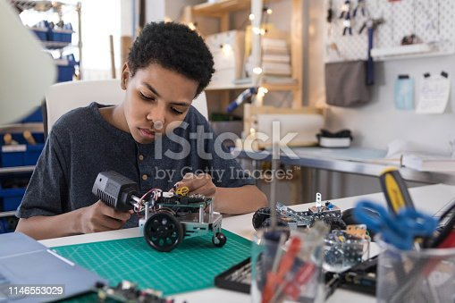 A serious teen boy uses a soldering gun to connect wires as he builds a robot at home.