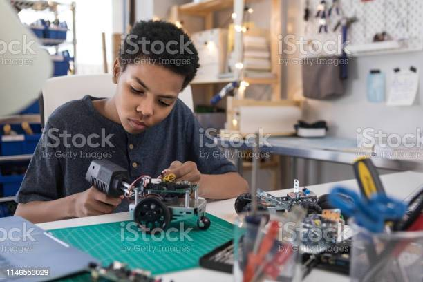 Teen Boy Solders Wires To Build Robot Stock Photo - Download Image Now