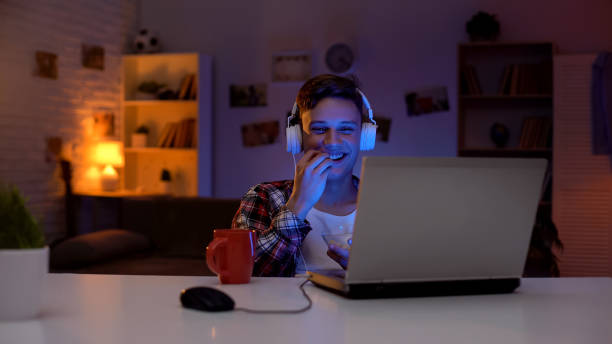 Teen boy watching funny show on laptop, eating snacks at leisure time, weekend stock photo