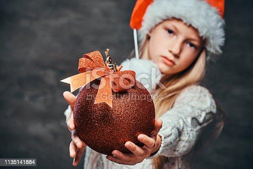 istock Teen boy wearing Santa's hat holding a big Christmas ball on a dark textured background. 1135141884