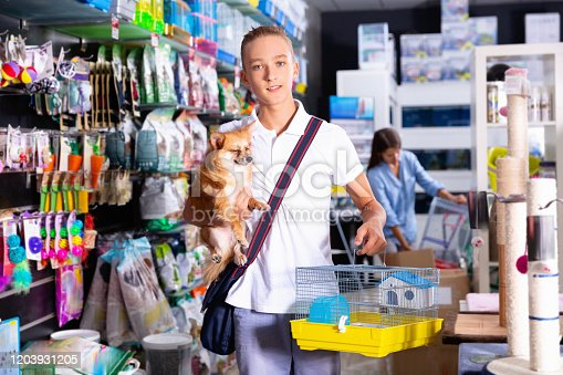 Cheerful positive  teen boy with dog is looking a cage for canary bird  in pet shop