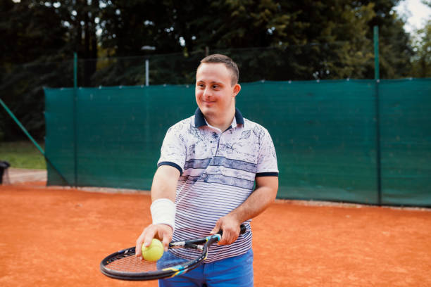 Teen boy with Down syndrome on tennis court stock photo