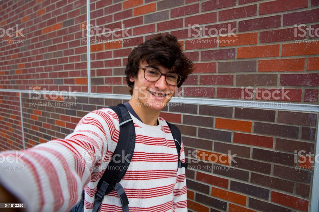 Teen Boy With Glasses Taking Selfie Smiling with Teeth and Peace Sign stock photo