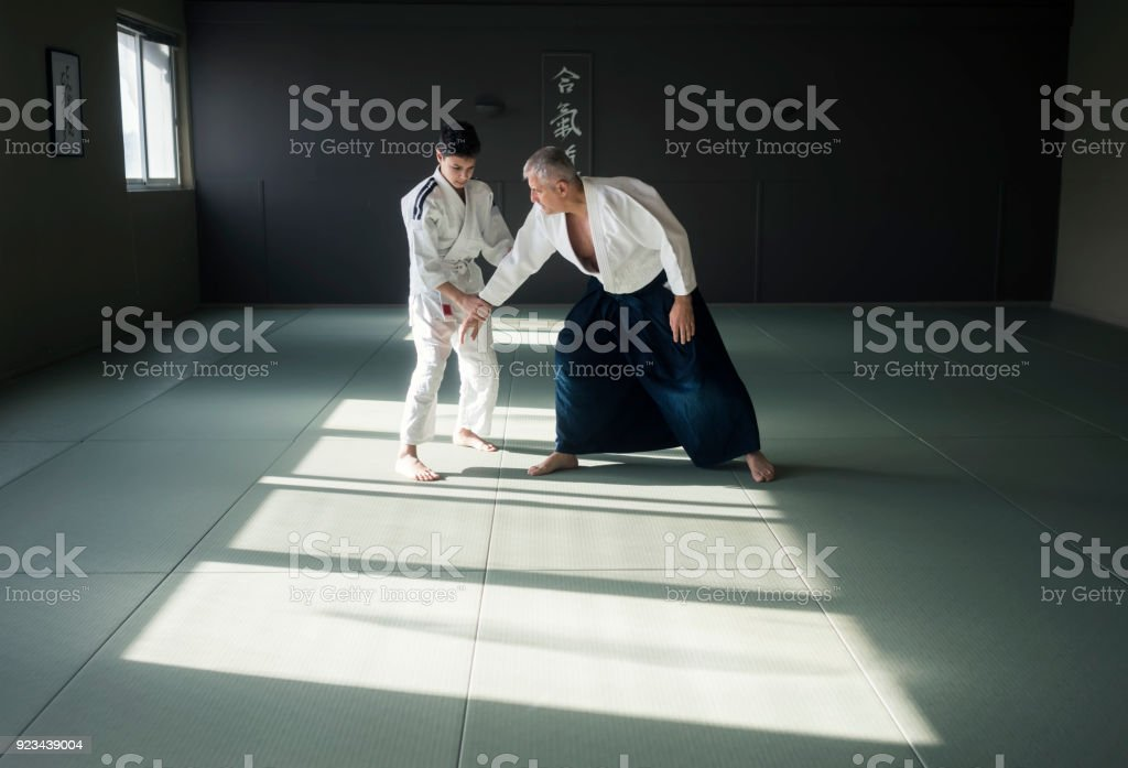 Teen boy with his sansei practicing in dojo стоковое фото