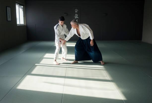 Teen boy with his sansei practicing in dojo stock photo