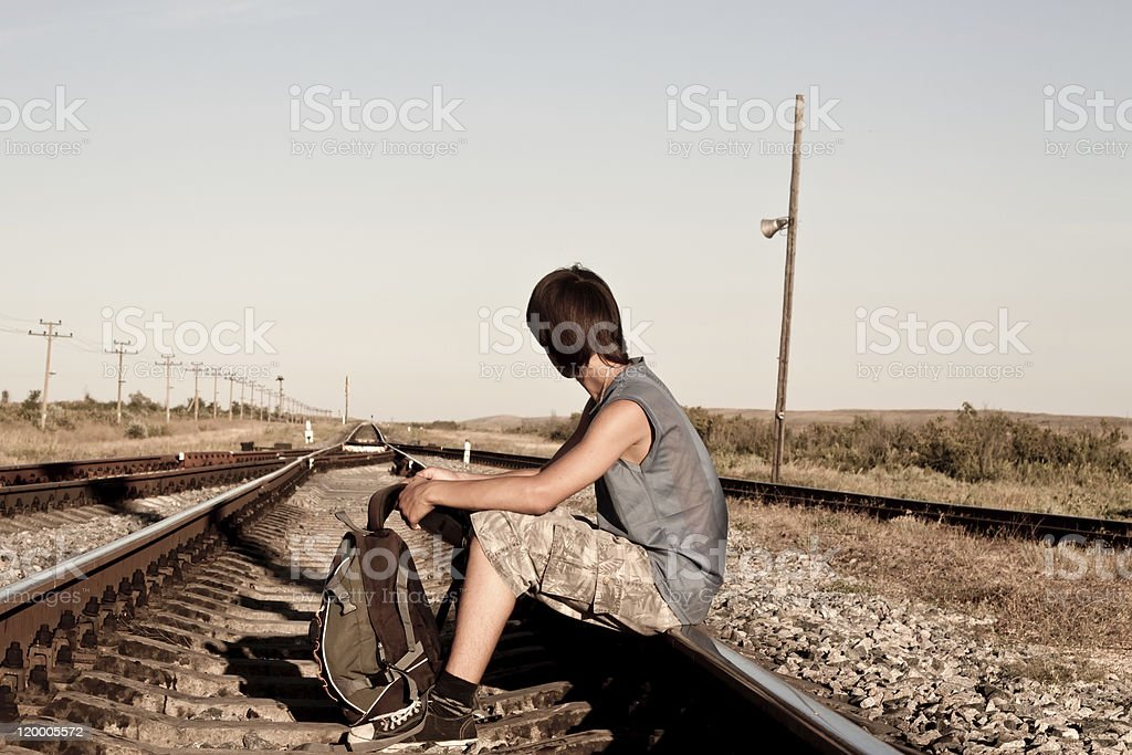 Teen boy with problems siting on rail road royalty-free stock photo