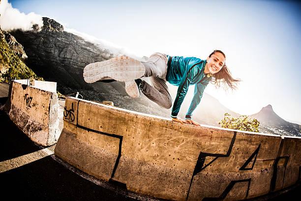 teen breakdance mädchen, die ein parkour- springen über eine wand - parkour stock-fotos und bilder