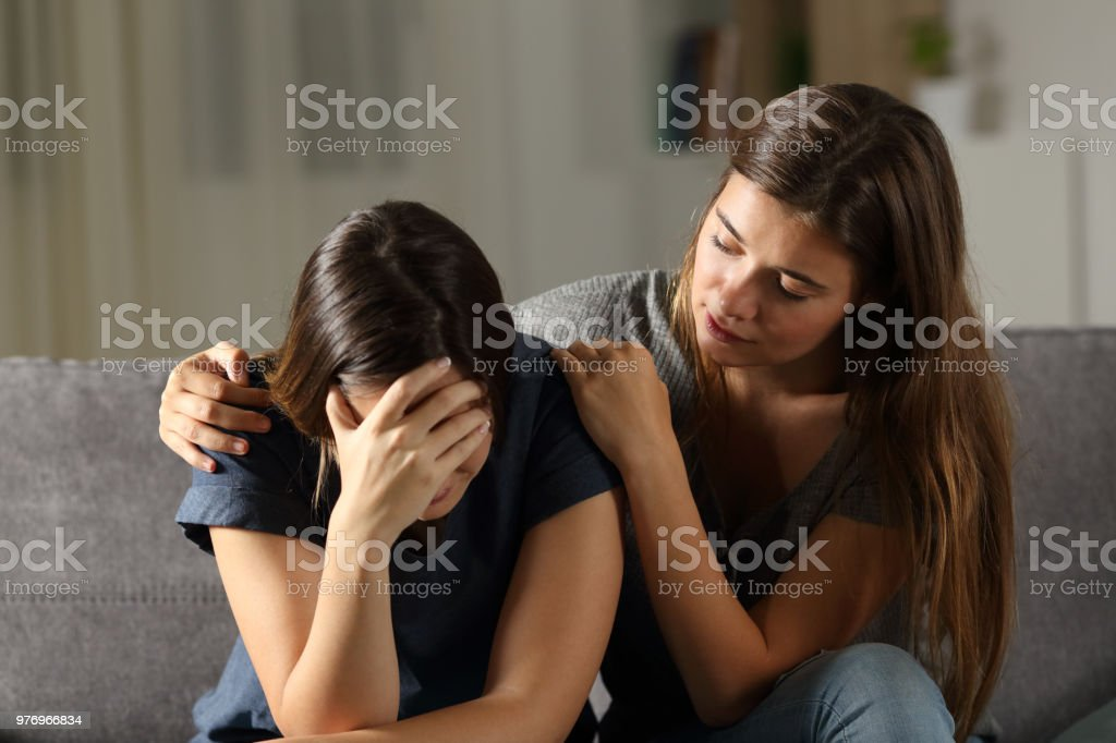 Teen comforting hes sad friend in the night stock photo