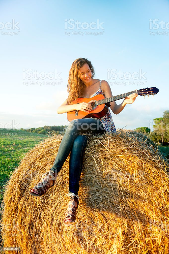 Teen country girl playing guitar - Stock image .
